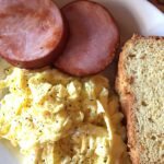 plate of breakfast food eggs ham and bread